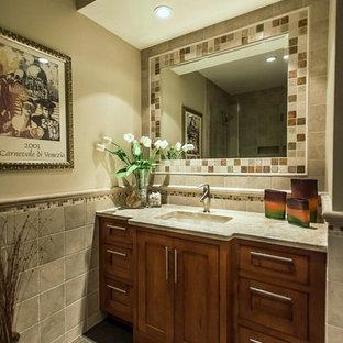 Idées déco pour un WC et toilettes classique de taille moyenne avec un placard à porte shaker, des portes de placard en bois brun, des carreaux de céramique, un mur gris, un lavabo encastré, un sol en ardoise, un plan de toilette en stéatite, un sol gris et un plan de toilette beige.