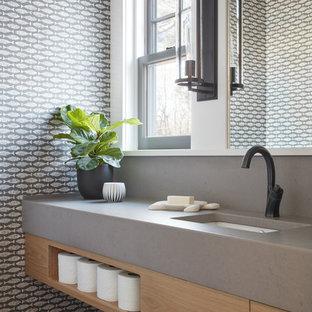 Réalisation d'un WC et toilettes marin avec un placard à porte plane, des portes de placard en bois clair, un mur multicolore, un lavabo encastré, un sol gris et un plan de toilette gris.