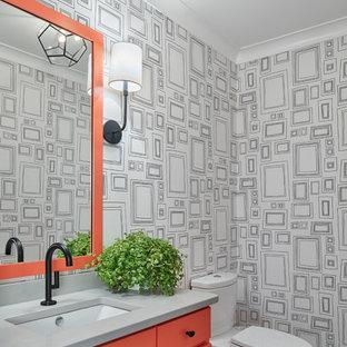 Modelo de aseo marinero con puertas de armario naranjas, sanitario de dos piezas, paredes multicolor, lavabo bajoencimera, suelo gris y encimeras grises