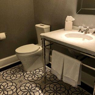 Foto på ett litet lantligt vit toalett, med en toalettstol med separat cisternkåpa, grå väggar, mosaikgolv, ett konsol handfat, marmorbänkskiva och grått golv