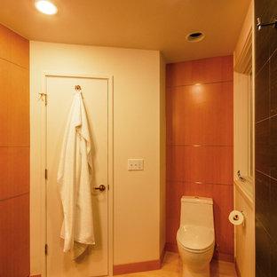 Стильный дизайн: маленький туалет в современном стиле с унитазом-моноблоком, черной плиткой, керамической плиткой, белыми стенами, полом из галечной плитки, раковиной с пьедесталом и коричневым полом - последний тренд