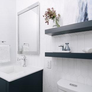Immagine di un piccolo bagno di servizio contemporaneo con ante blu, WC a due pezzi, piastrelle bianche, piastrelle in ceramica, pareti grigie, top in quarzo composito, top bianco, ante lisce, lavabo integrato, pavimento in gres porcellanato e pavimento grigio