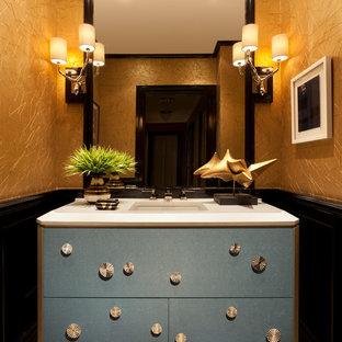 Idées déco pour un WC et toilettes classique de taille moyenne avec un placard en trompe-l'oeil, des portes de placard bleues, un mur noir, un sol en carrelage de terre cuite, un lavabo intégré, un plan de toilette en surface solide et un sol beige.