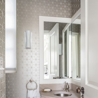 Inspiration for a transitional powder room remodel in New York with an undermount sink, recessed-panel cabinets, white cabinets and beige countertops