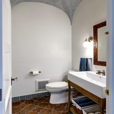 Powder room - mid-sized mediterranean terra-cotta tile and multicolored floor powder room idea in Los Angeles with open cabinets, a trough sink, medium tone wood cabinets, a two-piece toilet, white walls and solid surface countertops