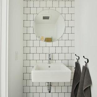 Idées déco pour un petit WC et toilettes industriel avec un mur blanc, un lavabo suspendu, un carrelage blanc, des carreaux de céramique et un sol noir.