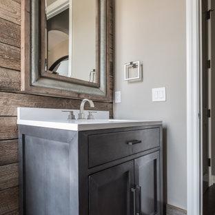 デトロイトの中くらいのおしゃれなトイレ・洗面所 (落し込みパネル扉のキャビネット、グレーのキャビネット、ベージュの壁、木目調タイルの床、茶色い床、白い洗面カウンター、造り付け洗面台、塗装板張りの壁) の写真