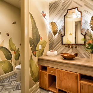 Island style gray floor powder room photo in Los Angeles with flat-panel cabinets, medium tone wood cabinets, multicolored walls, a vessel sink and beige countertops