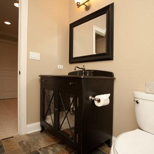 Kleine Klassische Gästetoilette mit Glasfronten, dunklen Holzschränken, Wandtoilette mit Spülkasten, beiger Wandfarbe, Schieferboden und braunen Fliesen in Chicago