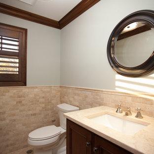 Immagine di un piccolo bagno di servizio design con ante con riquadro incassato, ante in legno bruno, WC a due pezzi, piastrelle beige, piastrelle in pietra, pareti blu, pavimento in travertino, lavabo sottopiano e top in travertino