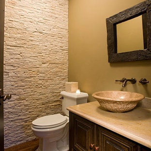 Example of a small mountain style medium tone wood floor powder room design in Chicago with raised-panel cabinets, dark wood cabinets, a two-piece toilet, beige walls, a vessel sink and marble countertops