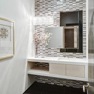 На фото: с высоким бюджетом туалеты среднего размера в современном стиле с врезной раковиной, серой плиткой, коричневой плиткой, открытыми фасадами, светлыми деревянными фасадами, белыми стенами, полом из известняка, керамогранитной плиткой и белой столешницей