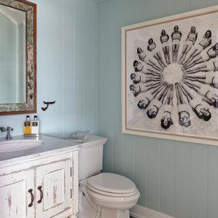 Foto di un bagno di servizio stile marino con consolle stile comò, ante con finitura invecchiata, pareti blu, pavimento con piastrelle a mosaico, lavabo sottopiano, pavimento nero e top bianco