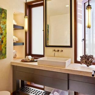 ロサンゼルスのコンテンポラリースタイルのおしゃれなトイレ・洗面所 (ベッセル式洗面器、濃色木目調キャビネット、ライムストーンの洗面台、ベージュのタイル、ベージュの壁、ライムストーンの床、フラットパネル扉のキャビネット) の写真