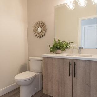 Foto di un bagno di servizio contemporaneo di medie dimensioni con ante lisce, ante in legno chiaro, WC monopezzo, pistrelle in bianco e nero, piastrelle in ceramica, pareti beige, pavimento in vinile, lavabo sottopiano, top in quarzo composito, pavimento grigio e top bianco