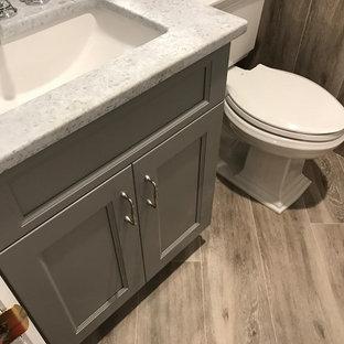 Foto di un piccolo bagno di servizio chic con ante in stile shaker, ante grigie, WC a due pezzi, pavimento in legno massello medio, lavabo sottopiano, top in granito, piastrelle grigie, piastrelle in pietra, pareti grigie, pavimento marrone e top grigio