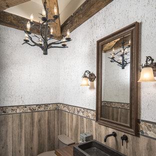 Пример оригинального дизайна: туалет среднего размера в стиле рустика с разноцветной плиткой, галечной плиткой, разноцветными стенами, настольной раковиной, столешницей из дерева и коричневой столешницей