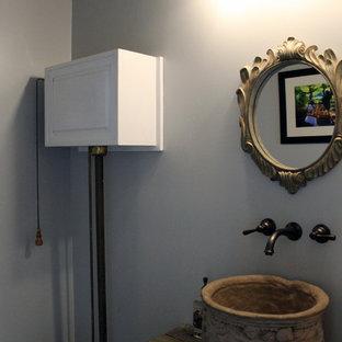 Diseño de aseo romántico, pequeño, con puertas de armario con efecto envejecido, paredes grises, lavabo sobreencimera y encimera de madera