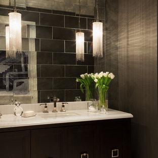 マイアミの中くらいのトランジショナルスタイルのおしゃれなトイレ・洗面所 (落し込みパネル扉のキャビネット、濃色木目調キャビネット、ミラータイル、茶色い壁、一体型シンク、大理石の洗面台、セラミックタイルの床、ベージュの床) の写真