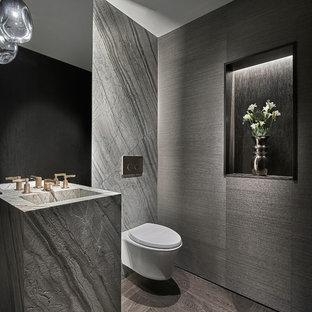 На фото: туалет в современном стиле с серой плиткой, плиткой из листового камня, серыми стенами, раковиной с пьедесталом и коричневым полом с