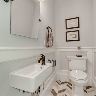 Medium sized traditional cloakroom in DC Metro with a two-piece toilet, multi-coloured tiles, stone tiles, grey walls, limestone flooring and a wall-mounted sink.