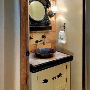 Пример оригинального дизайна: маленький туалет в средиземноморском стиле с настольной раковиной, фасадами островного типа, желтыми фасадами, столешницей из плитки, оранжевой плиткой, терракотовой плиткой, бежевыми стенами и полом из терракотовой плитки