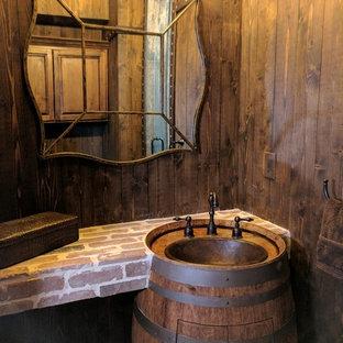 Пример оригинального дизайна: маленький туалет в стиле рустика с фасадами с выступающей филенкой, фасадами цвета дерева среднего тона, унитазом-моноблоком, коричневыми стенами, кирпичным полом, монолитной раковиной и красным полом