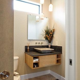 Réalisation d'un petit WC et toilettes design avec un placard à porte plane, des portes de placard en bois clair, un WC séparé, un mur beige, un sol en travertin, une vasque, un plan de toilette en granite et un sol beige.