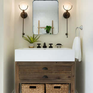 Design ideas for a medium sized rural cloakroom in Minneapolis with flat-panel cabinets, dark wood cabinets, beige walls, travertine flooring, an integrated sink and brown floors.