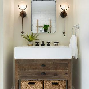 Cette image montre un WC et toilettes rustique de taille moyenne avec un placard à porte plane, des portes de placard en bois sombre, un mur beige, un sol en travertin, un lavabo intégré et un sol marron.