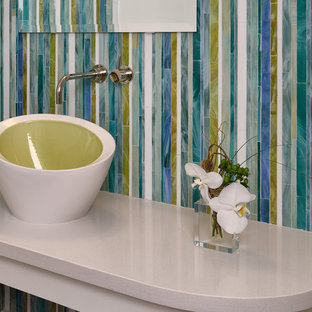 Photo of a small contemporary cloakroom in San Diego with a one-piece toilet, multi-coloured tiles, glass tiles, white walls, medium hardwood flooring, a vessel sink, solid surface worktops and brown floors.