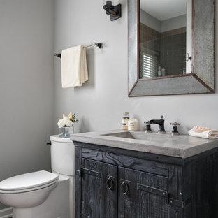 На фото: маленький туалет с фасадами островного типа, черными фасадами, унитазом-моноблоком, серыми стенами, полом из керамогранита, монолитной раковиной, столешницей из бетона и разноцветным полом с