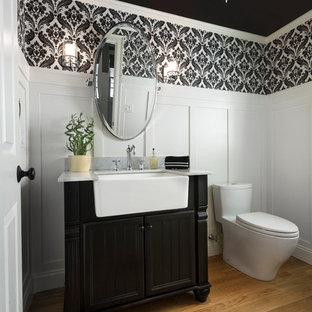 Idée de décoration pour un WC et toilettes tradition de taille moyenne avec un placard en trompe-l'oeil, des portes de placard noires, un plan de toilette en quartz, un sol en bois brun et un mur multicolore.