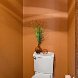 Foto de aseo moderno, pequeño, con lavabo integrado, armarios con paneles lisos, puertas de armario de madera oscura, sanitario de dos piezas, parades naranjas, suelo de baldosas de porcelana y baldosas y/o azulejos grises