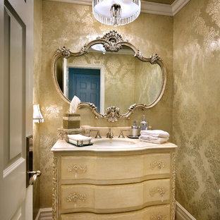 Cette photo montre un petit WC et toilettes chic avec un placard en trompe-l'oeil, des portes de placard beiges, un WC séparé, un carrelage beige, un sol en travertin, un lavabo encastré, un plan de toilette en marbre et un mur jaune.
