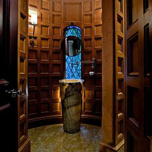 Создайте стильный интерьер: туалет среднего размера в классическом стиле с раковиной с пьедесталом, фасадами цвета дерева среднего тона, столешницей из оникса, коричневыми стенами и мраморным полом - последний тренд