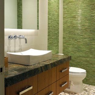 На фото: маленький туалет в современном стиле с настольной раковиной, плоскими фасадами, фасадами цвета дерева среднего тона, столешницей из гранита, раздельным унитазом, белой плиткой, зеленой плиткой, керамогранитной плиткой, зелеными стенами, полом из керамогранита, бежевым полом и серой столешницей с