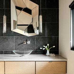 オースティンの中くらいのコンテンポラリースタイルのおしゃれなトイレ・洗面所 (フラットパネル扉のキャビネット、淡色木目調キャビネット、黒いタイル、ライムストーンタイル、黒い壁、コンクリートの床、ベッセル式洗面器、珪岩の洗面台、グレーの床、白い洗面カウンター、フローティング洗面台、板張り天井) の写真