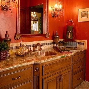 Неиссякаемый источник вдохновения для домашнего уюта: большой туалет в средиземноморском стиле с фасадами островного типа, фасадами цвета дерева среднего тона, разноцветной плиткой, красными стенами, полом из травертина, накладной раковиной и столешницей из искусственного кварца