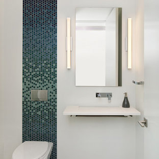 This is an example of a medium sized contemporary cloakroom in Tampa with open cabinets, a wall mounted toilet, multi-coloured tiles, blue tiles, mosaic tiles, white walls, porcelain flooring, a wall-mounted sink, engineered stone worktops, grey floors and white worktops.