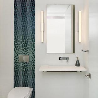 Inspiration pour un WC et toilettes design de taille moyenne avec un placard sans porte, un WC suspendu, un carrelage multicolore, un carrelage bleu, carrelage en mosaïque, un mur blanc, un sol en carrelage de porcelaine, un lavabo suspendu, un plan de toilette en quartz modifié, un sol gris et un plan de toilette blanc.