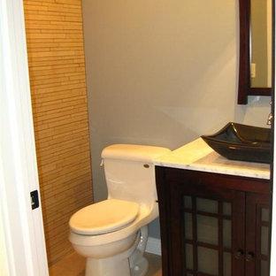 Modelo de aseo asiático, de tamaño medio, con armarios tipo mueble, puertas de armario de madera en tonos medios, sanitario de una pieza, paredes beige, lavabo sobreencimera y encimera de cuarzo compacto