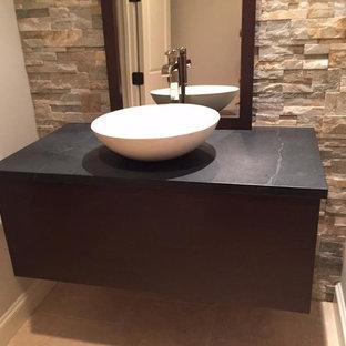 Пример оригинального дизайна: маленький туалет в современном стиле с плоскими фасадами, черными фасадами, бежевыми стенами, полом из керамической плитки, раковиной с пьедесталом, бежевой плиткой, каменной плиткой, столешницей из талькохлорита и бежевым полом