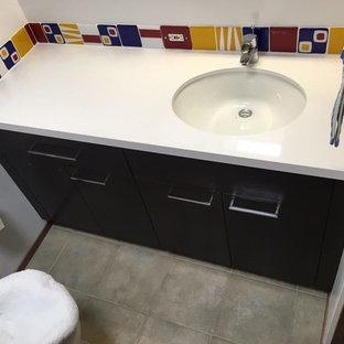 Cette image montre un petit WC et toilettes bohème avec un placard à porte plane, des portes de placard noires, un WC séparé, un carrelage bleu, un carrelage multicolore, un carrelage rouge, un carrelage blanc, un carrelage jaune, des carreaux de céramique, un mur blanc, un sol en carreaux de ciment, un lavabo encastré, un plan de toilette en surface solide et un sol gris.