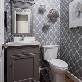 Esempio di un piccolo bagno di servizio tradizionale con ante a filo, ante grigie, WC a due pezzi, pareti verdi, pavimento in legno massello medio, lavabo sottopiano, top in quarzo composito e pavimento marrone