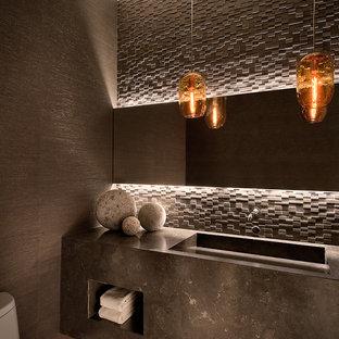 Diseño de aseo actual con lavabo integrado, baldosas y/o azulejos de piedra y encimeras grises