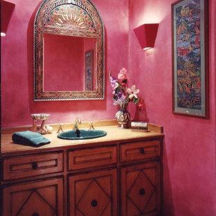 Kleine Stilmix Gästetoilette mit Einbauwaschbecken, profilierten Schrankfronten, Waschtisch aus Holz, Wandtoilette mit Spülkasten, braunem Holzboden, rosa Wandfarbe und dunklen Holzschränken in Los Angeles