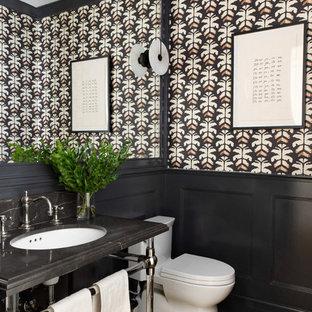 Inredning av ett klassiskt stort svart svart toalett, med en toalettstol med hel cisternkåpa, ljust trägolv, beiget golv, flerfärgade väggar och ett undermonterad handfat