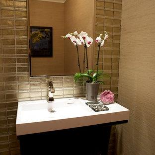 На фото: с высоким бюджетом маленькие туалеты в современном стиле с стеклянной плиткой, бежевыми стенами, темным паркетным полом и монолитной раковиной