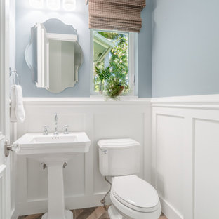 マイアミの小さいトランジショナルスタイルのおしゃれなトイレ・洗面所 (青い壁、磁器タイルの床、茶色い床、白い洗面カウンター、分離型トイレ、ペデスタルシンク、羽目板の壁) の写真